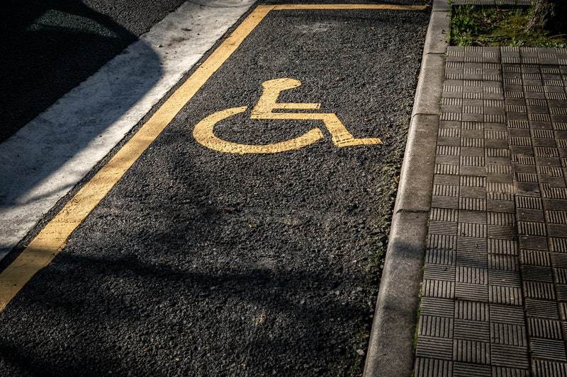 Photo of a handicapped parking lot with the dummy painted in yellow when it should be blue.
