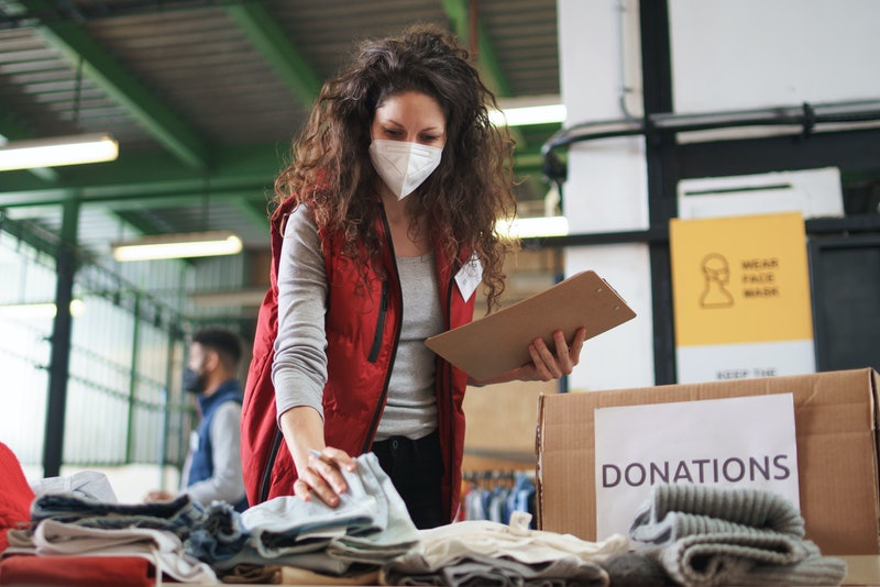 Woman with face mask sorting clothes while volunteering to help people affected by the coronavirus pandemic.