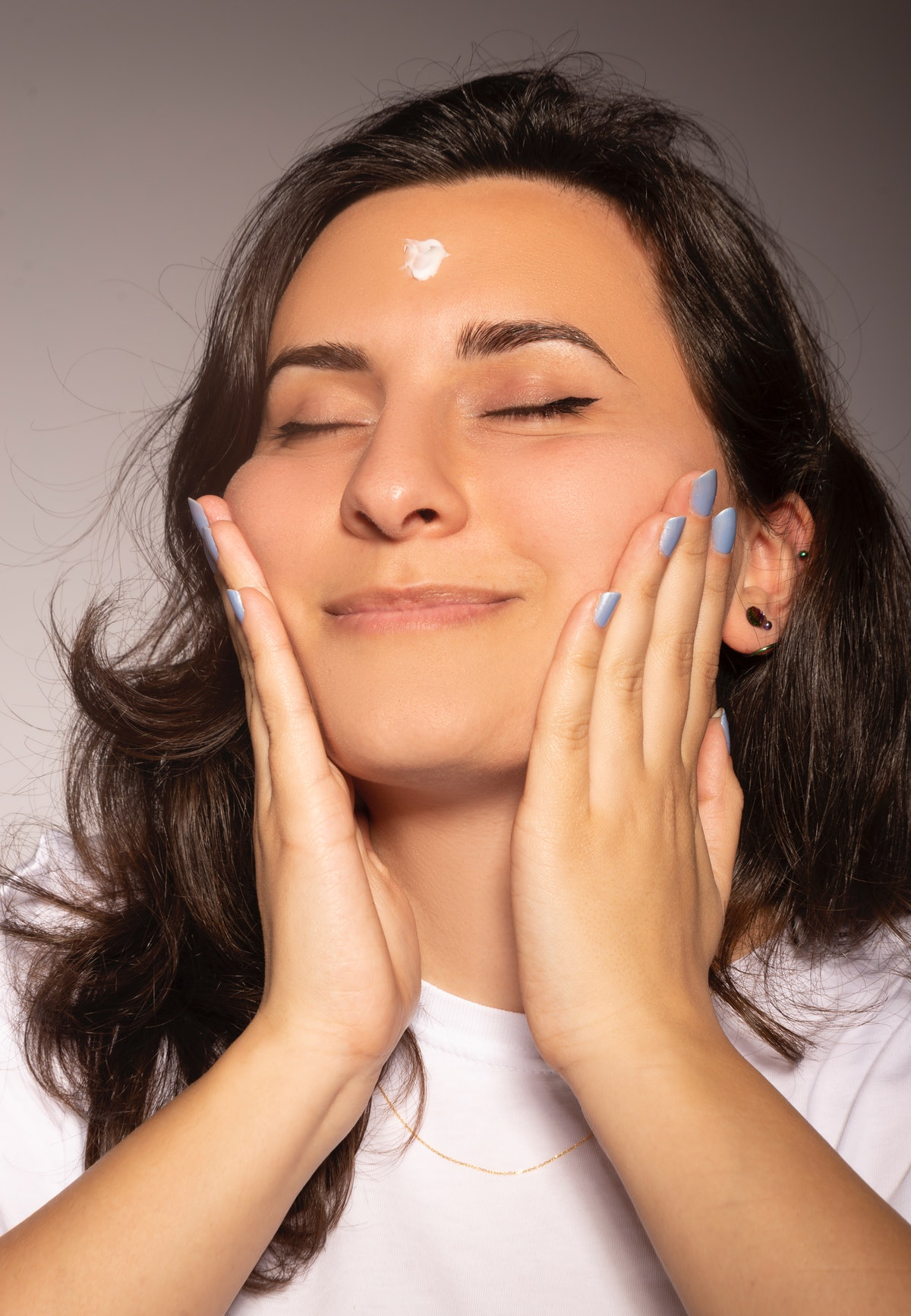 Perfectly beautiful woman wears skincare cream on her face in peace with her eyes closed.