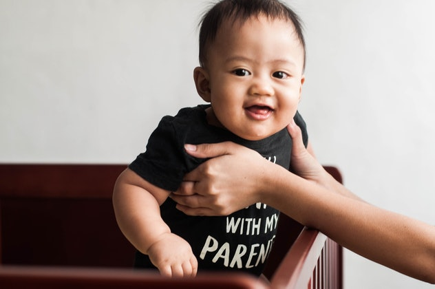 A waist-up portrait of a Southeast Asian baby boy walking on the crib with assistance of his mother
