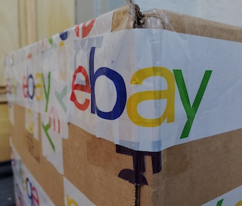 Close-up of the eBay logo featured on the packing tape securing a large cardboard shipping box in Sa...