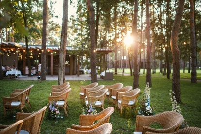 Place of the wedding ceremony at sunset in the open air. Wicker chairs stand under luminous yellow l...