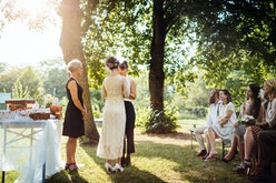 Lesbian couple holding hands in front of the altar. The wedding is outdoors and guest are seated in ...