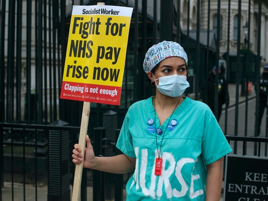 Nurse holds a sign outside of Downing Street, Nurses are threatening to strike after being offered a 1% pay rise by the government amid the Covid-19 pandemic on Sunday 7th March 2021. (Photo by Lucy North/MI News/NurPhoto via Getty Images)