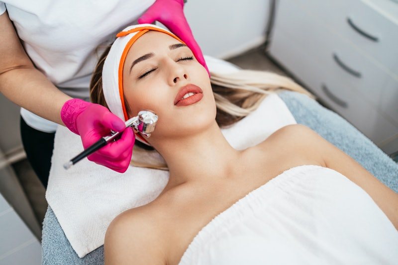 Beautiful and attractive adult woman receiving professional facial care steam beauty treatment