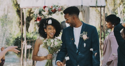 Cropped shot of a newlywed couple walking down the isle together after being announced as husband an...