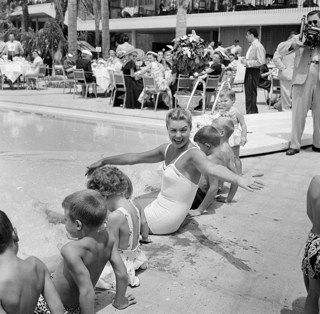 Actress Esther Williams sits pool side with children during the opening day of the Esther Williams S...