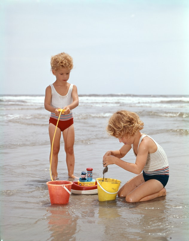 Kids playing on the beach in the 1960s.