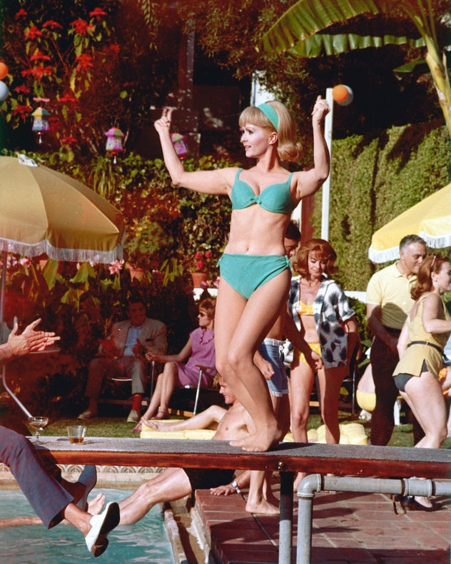 Debbie Reynolds wearing a blue bikini while dancing on a diving board over a swimming pool, circa 19...
