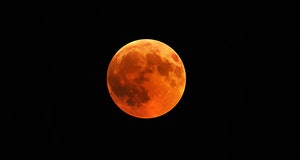 A beautiful shot of a red moon, total lunar eclipse with a black night sky in the background