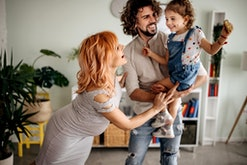 Pregnant woman, husband and daughter enjoy their house having fun