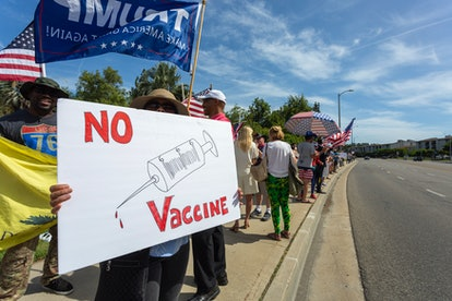 WOODLAND HILLS, CA - MAY 16: A protester holds an anti-vaccination sign as supporters of President D...