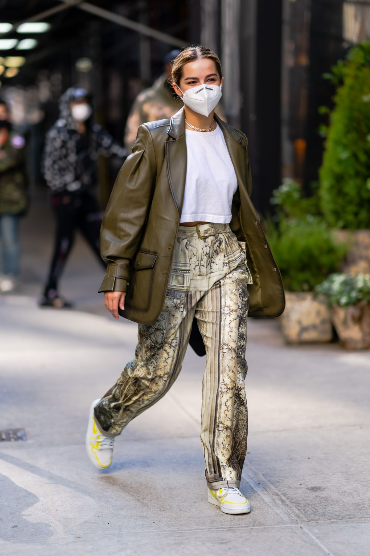 Addison Rae wears Baroque-print pants and a leather blazer on the street in one of her outfits to date.