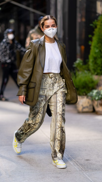 Addison Rae wears Baroque-print pants and a leather blazer on the street in one of her outfits to da...