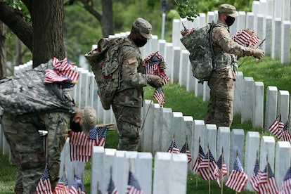 """ARLINGTON, VIRGINIA - MAY 21: Wearing face masks to reduce the risk of spreading the novel coronavirus, soldiers from the 3rd Infantry Regiment, also called the """"Old Guard,"""" place U.S. flags in front of every grave site ahead of the Memorial Day weekend in Arlington National Cemetery on May 21, 2020 in Arlington, Virginia. Traditionally known as """"Flags-In,"""" soldiers place small flags in front of more than 228,000 headstones and at the bottom of about 7,000 niche rows in the cemetery's Columbarium Courts and Niche Wall. (Photo by Chip Somodevilla/Getty Images)"""