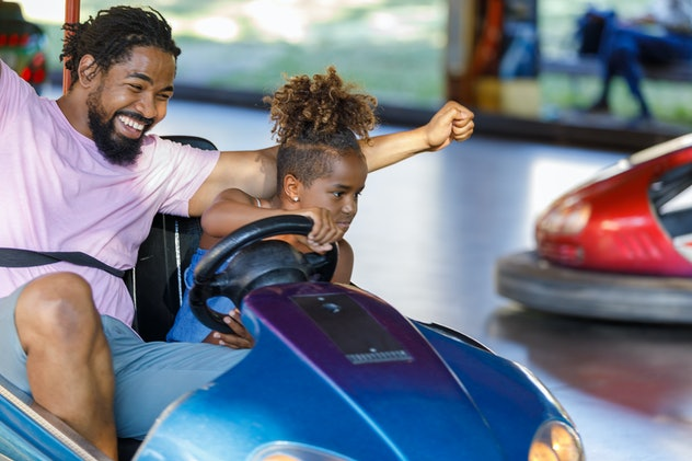 Father and Daughter of African-American Ethnicity are Spending a Wonderful Day While Driving in Bumper Car in Luna Park.