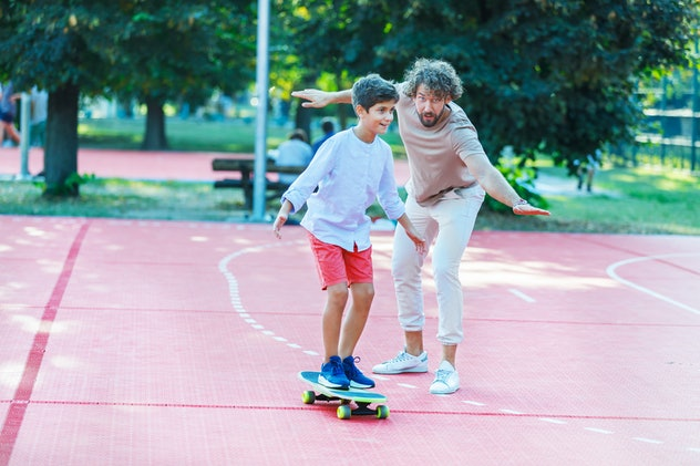 Cute Boy is Happy to Spend a Time on Skateboard With his Cheerful Father in Public Park.