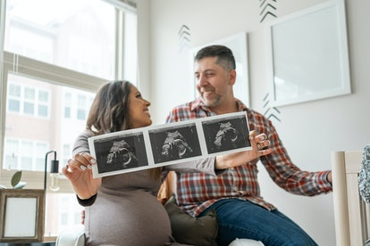 Couple holding an ultrasound celebrating the pregnancy