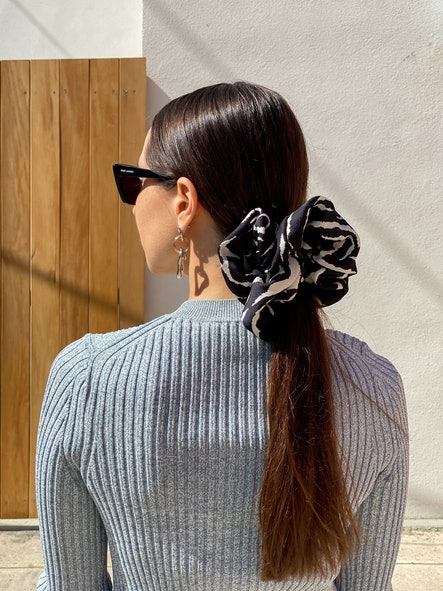 PARIS, FRANCE - MARCH 05: Julia Comil wears Saint Laurent YSL sunglasses, earrings, a wool gray rib top by Theory, a maxi black and white zebra print scrunchie by Autumn Adeigbo, during an online remote fashion photo session via Apple iphone / Facetime and the CLOS app as the model is based in Los Angeles - California and the photographer in Paris - France, on March 05, 2021 in Paris, France. (Photo by Edward Berthelot/Getty Images)