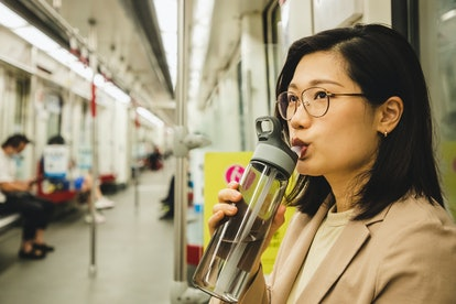asian businesswoman drinking water from a reusable water bottle in the subway