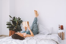 A woman reads a book in bed while stretching her legs up a wall. These believable excuses to cancel plans will let you stay home and read.