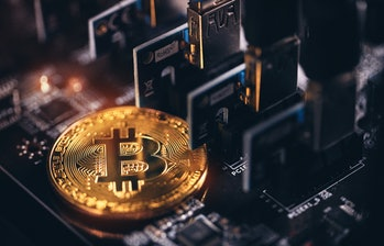 Studio shot of a Bitcoin   virtual currency with an electronic / computer circuit board background. Russia, Moscow