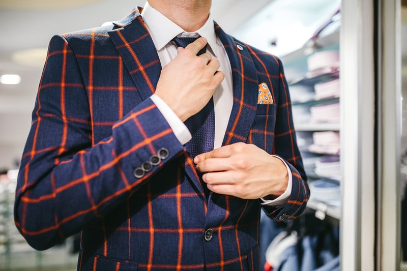 Young caucasian man trying suit and adjusting necktie in suit shop.