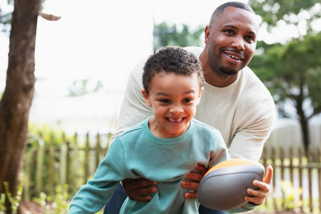 A little boy having fun playing with his father in the backyard. He is holding a football, smiling as dad catches him. The African-American man is in his 30s. His son, 5 years old, is mixed race African-American and Caucasian. The focus is on the father.