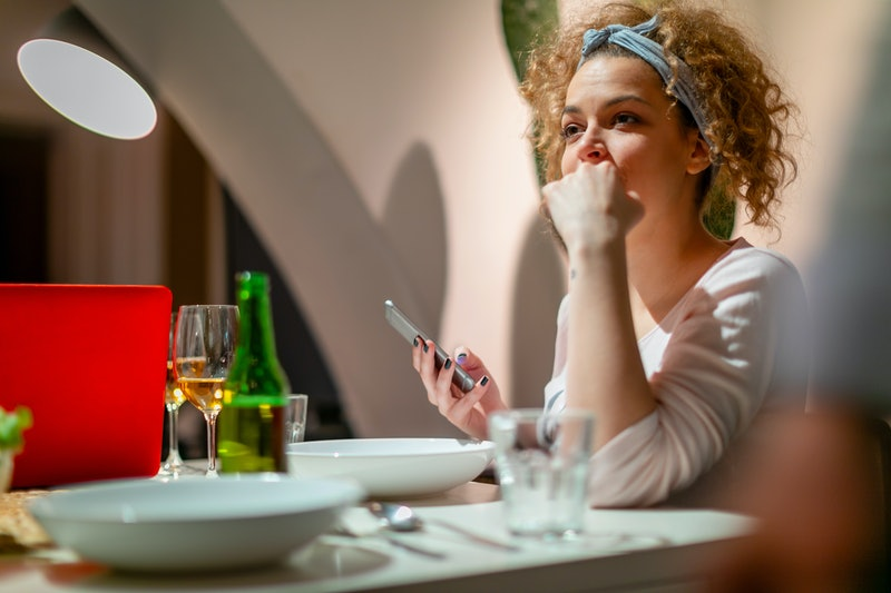 Young millennial woman sitting at the dining table, thinking about the signs her parents were emotionally abusive during her childhood.