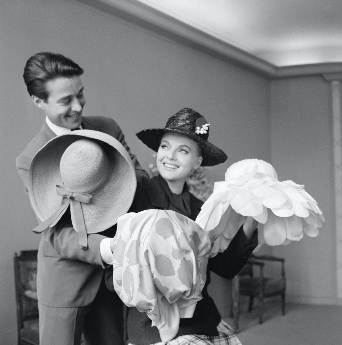 Fashion designer Halston and Italian film star Virna Lisi look at various hats.