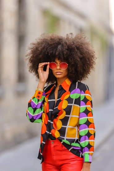 PARIS, FRANCE - MAY 03: Alicia Aylies wears red and gold Bottega Veneta sunglasses, a gold chain pendant necklace, a black with red orange purple and green pattern Lanvin silk shirt, red shiny leather Nice Piece Vintage pants, a gold with blue stone bracelet, on May 03, 2021 in Paris, France. (Photo by Edward Berthelot/Getty Images)