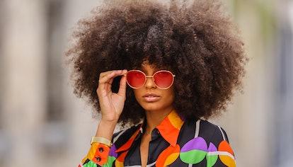 PARIS, FRANCE - MAY 03: Alicia Aylies wears red and gold Bottega Veneta sunglasses, a gold chain pen...
