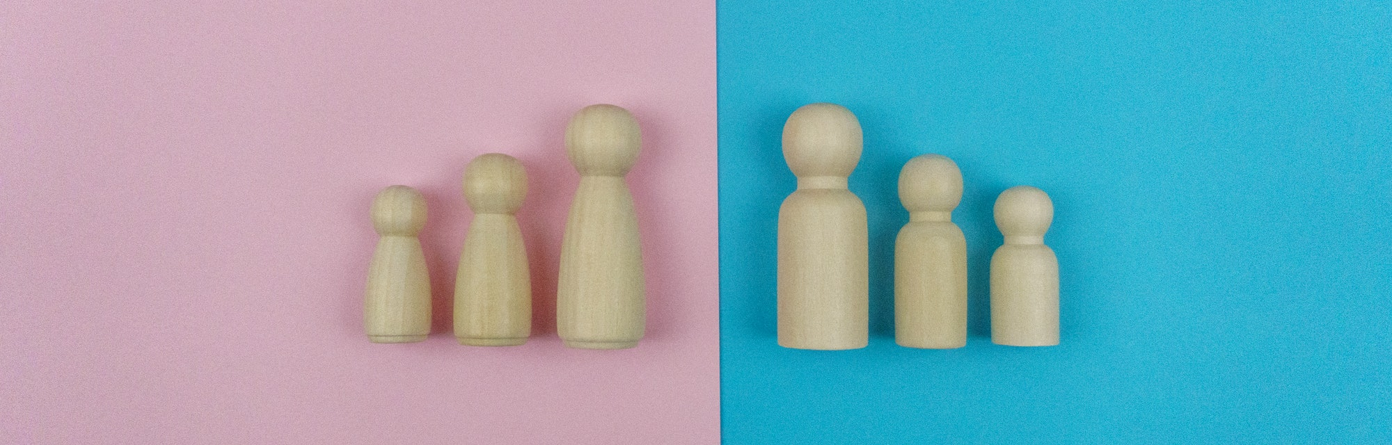 Still life image, Wooden figures family of four on Blue and Pink background.