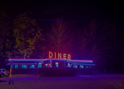 Illuminated signage and lighting at night at Martindale Chief Diner, Craryville, Columbia County, New York, USA.  The building is made of steel and glass with big red DINER letters on top.  This diner is known as Silk City #5807, manufactured by Patterson Vehicle Co, Paterson, NJ, producer of lowest cost diners from 1927-1964.  The Martindale owner Bert Coons had a chain of diners along the Taconic State Pkwy