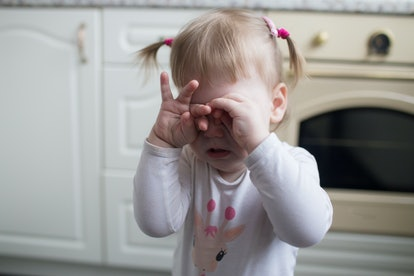 Toddler girl covered her eyes with her hands and crying