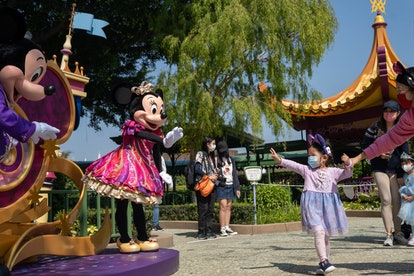 HONG KONG, CHINA - 2021/02/19: A child interacts with the actors dressed as the Disney cartoon characters Mickey Mouse and Minnie Mouse while maintaining social distance between them during the reopening of the Hong Kong Disneyland Resort. The Hong Kong Disneyland Resort reopens its door to visors as the city's government has relaxed the lockdown restrictions as the infection rate of the Covid-19 coronavirus has reduced significantly in recent days. (Photo by Geovien So/SOPA Images/LightRocket via Getty Images)