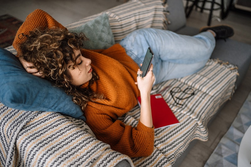 A woman lies on her couch texting a friend who's ignoring her.
