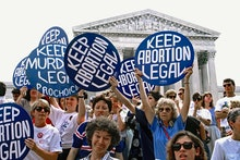Pro-life and pro-choice demonstrators hold signs on the steps of the Supreme Court building  The pro...