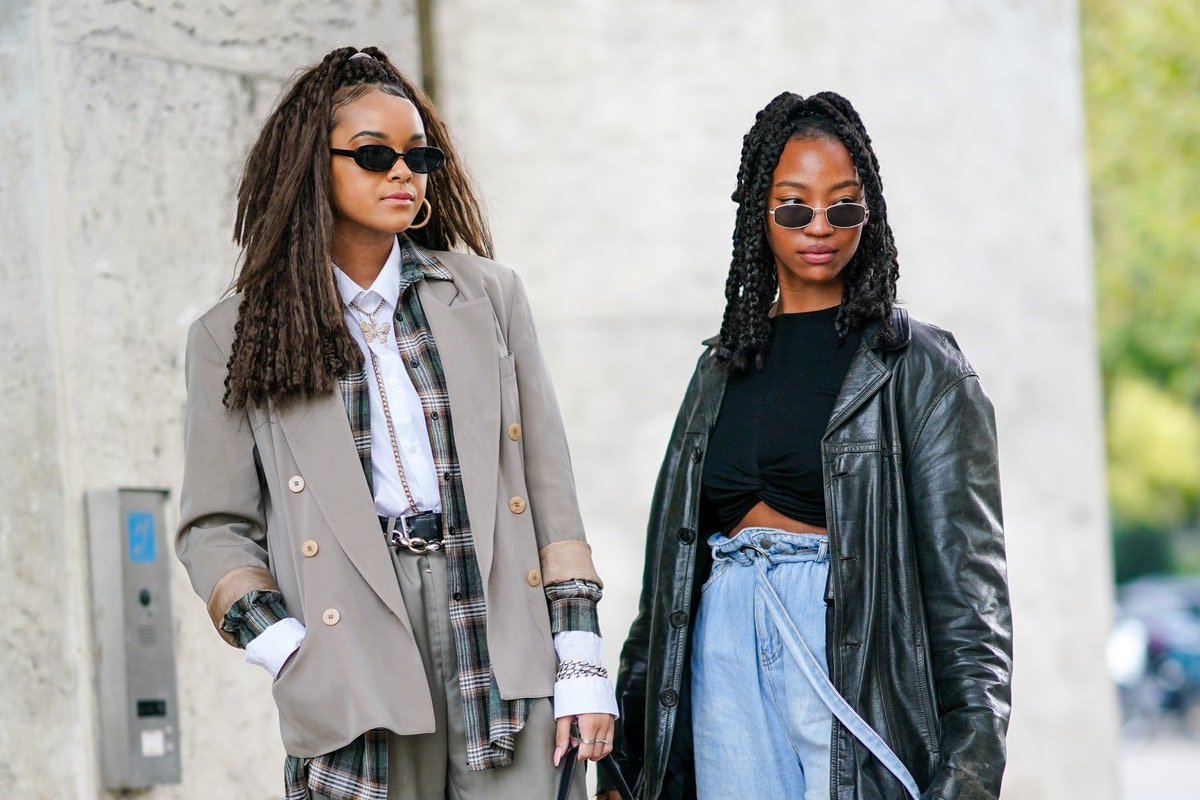 PARIS, FRANCE - OCTOBER 01: A guest (L) wears black sunglasses, a gold earring, a silver and gold rhinestone butterfly pendant necklace, a chain jewelry, a white shirt, a dark green white and camel checkered long oversized shirt, silver and rhinestones chain bracelets, silver rings, a black shiny leather belt, a beige long blazer jacket, pale green large flared pants, a black shiny leather Saddle Dior handbag, a guest (R) wears sunglasses, a black cotton crop-top, a black shiny leather oversized long coat, faded blue belted denim jean flared pants, outside Chloe, during Paris Fashion Week - Womenswear Spring Summer 2021, on October 01, 2020 in Paris, France. (Photo by Edward Berthelot/Getty Images)