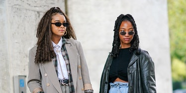 PARIS, FRANCE - OCTOBER 01: A guest (L) wears black sunglasses, a gold earring, a silver and gold rh...