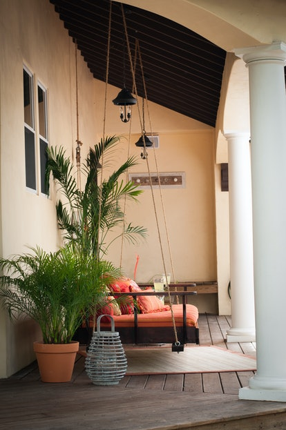 side view of orange upholstered swing chair on porch