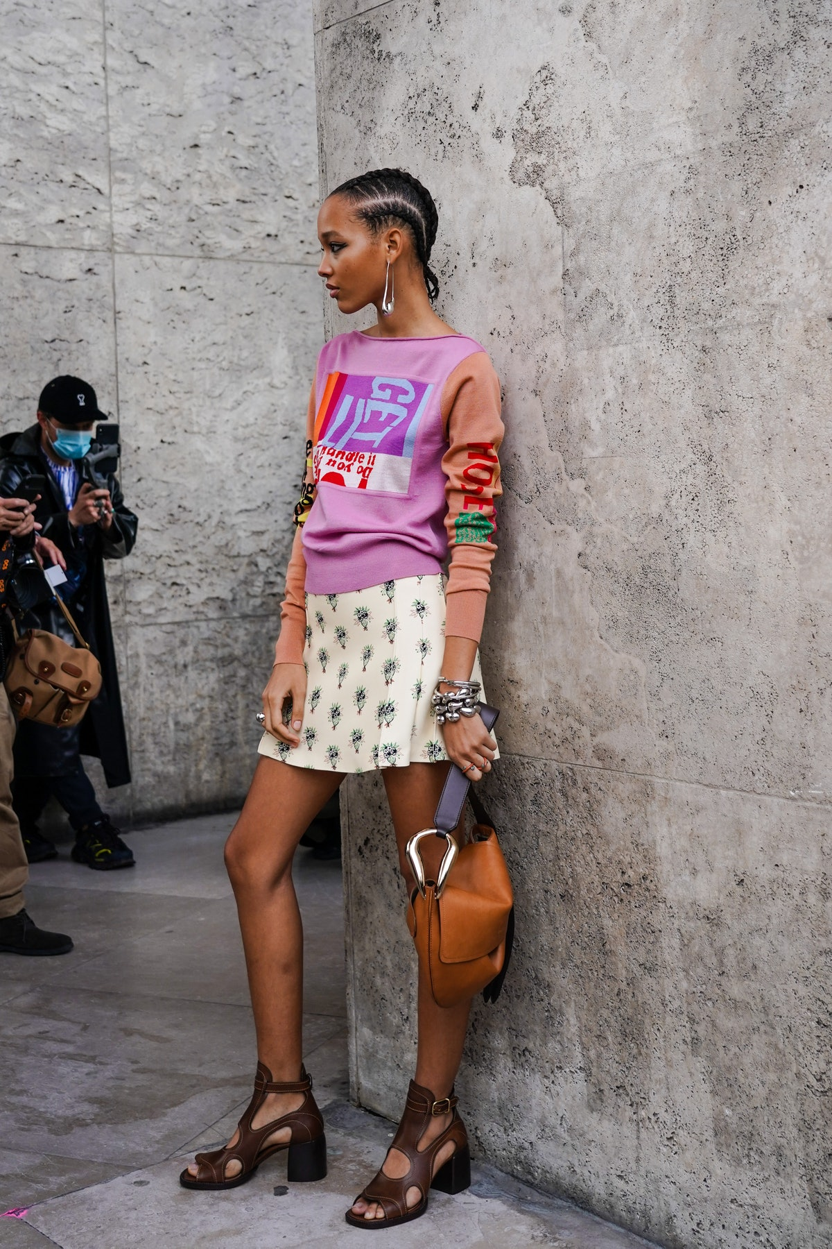 PARIS, FRANCE - OCTOBER 01: A guest wears an earring, rings, bracelets, a colorful top, a white mini skirt with green patterns, a Chloe bag, dark brown ankle-strap sandals with block heels, outside Chloe, during Paris Fashion Week - Womenswear Spring Summer 2021, on October 01, 2020 in Paris, France. (Photo by Edward Berthelot/Getty Images)