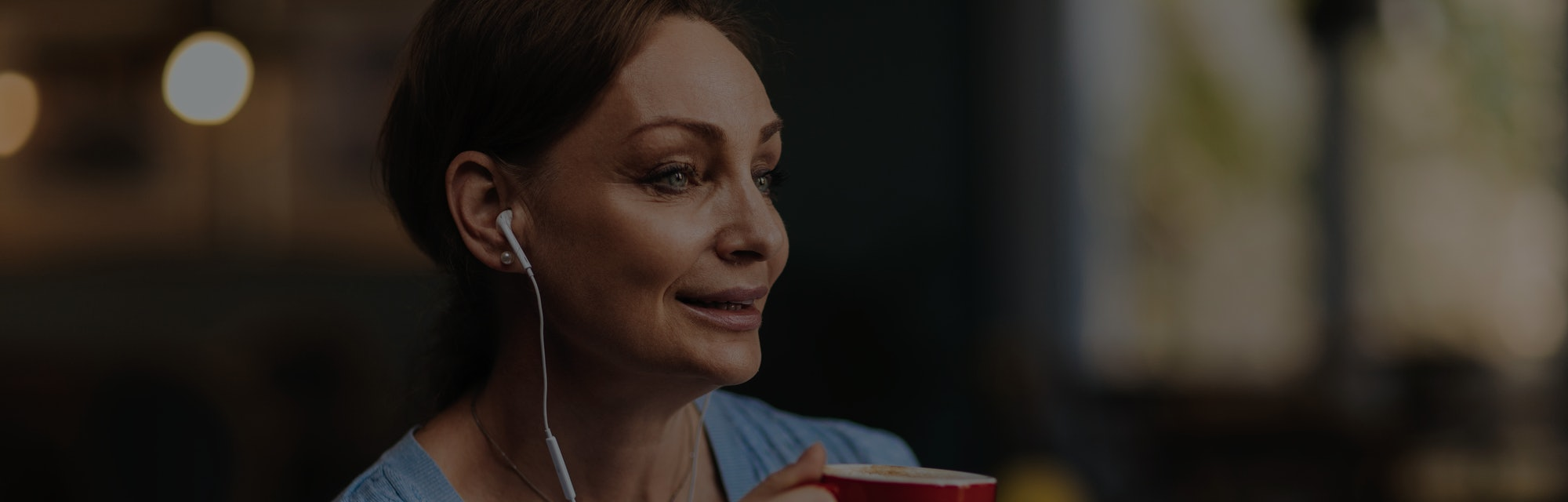 Beautiful brunette woman listening to music while having a coffee in her favourite shop