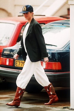 Princess Diana wearing an unusual combination of white trousers, boots, a blazer jacket and a baseba...