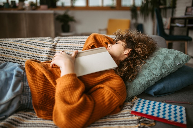 Young student woman taking a disco nap post-pandemic on the sofa in her living room after studying