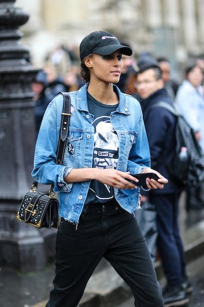PARIS, FRANCE - MARCH 04:  Cindy Bruna wears a cap, a blue denim jacket, and a Prada bag, outside th...