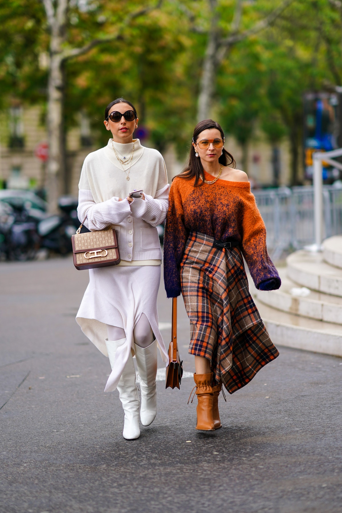 PARIS, FRANCE - OCTOBER 01: Gabriella Berdugo (L) wears sunglasses, necklaces, a cream color hi-neck sweater, a light mauve vest, a light mauve asymmetric skirt, a Carolina Herrera bag, white knee-high boots  ; Julia Comil (R) wears sunglasses, earrings, a golden necklace, an oversized orange and deep purple sweater, an asymmetric grey and orange plaid skirt, a brown bag, tan color pointy heeled mid-calf boots, outside Chloe, during Paris Fashion Week - Womenswear Spring Summer 2021, on October 01, 2020 in Paris, France. (Photo by Edward Berthelot/Getty Images)