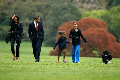 WASHINGTON - APRIL 14:  U.S. President Barack Obama (2nd L), first lady Michelle Obama (L) and his daughters, Sasha and Malia (R), introduce their new dog, a Portuguese water dog named Bo, to the White House press corps on the South Lawn of the White House April 14, 2009 in Washington, DC. The six-month-old puppy is a gift from Sen. Edward M. Kennedy (D-MA) who owns several Portuguese water dogs himself. This breed of dog is considered a good pet for children who have allergies, as Malia does.  (Photo by Chip Somodevilla/Getty Images)