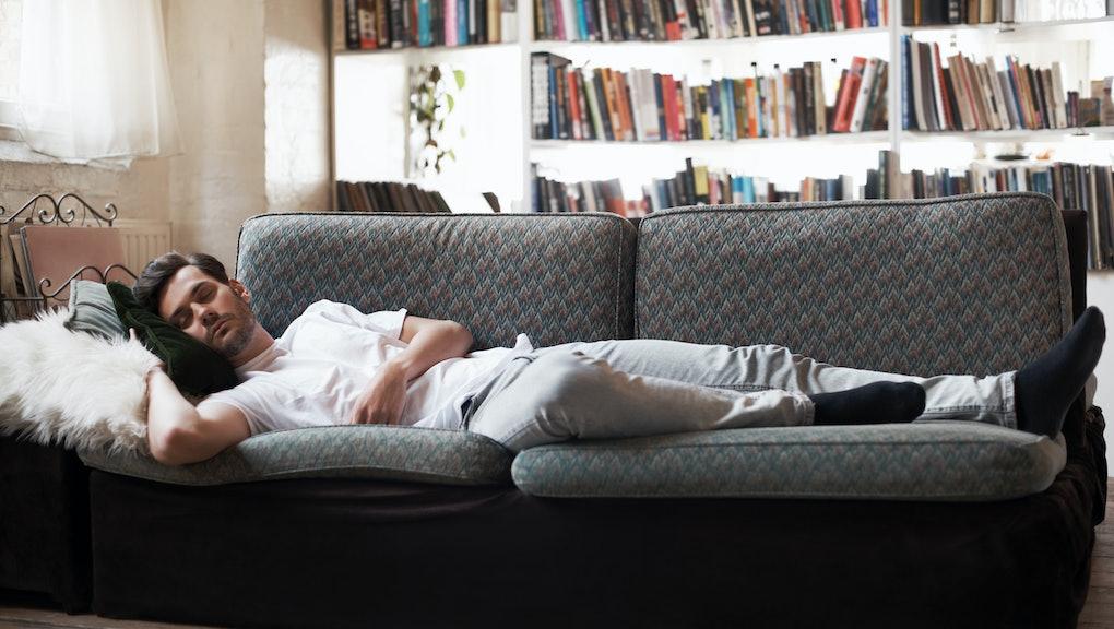 Man sleeping on sofa in cozy loft apartment