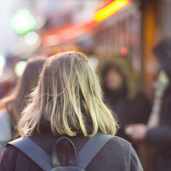 """A female backpacker walks through a city thinking, """"I feel so alone."""" Experts share reasons for feel..."""